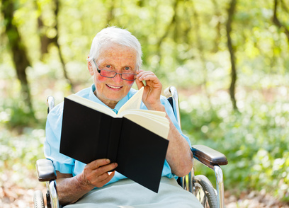 Elderly woman in wheelchair holding and reading a book.